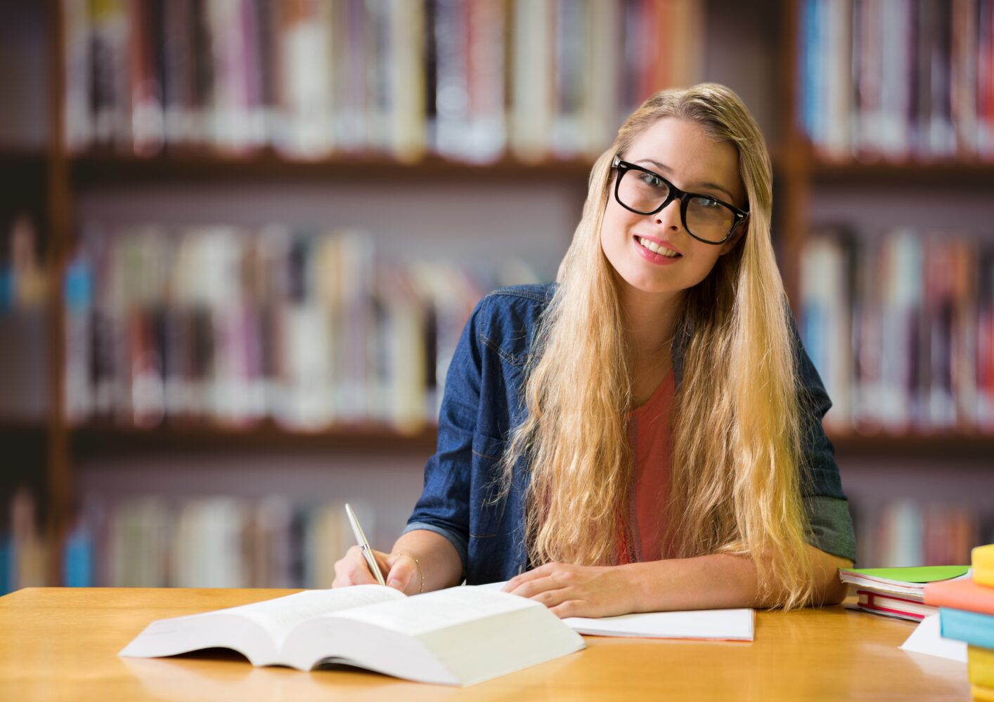 Portrait of girl in spectacles studying in library
